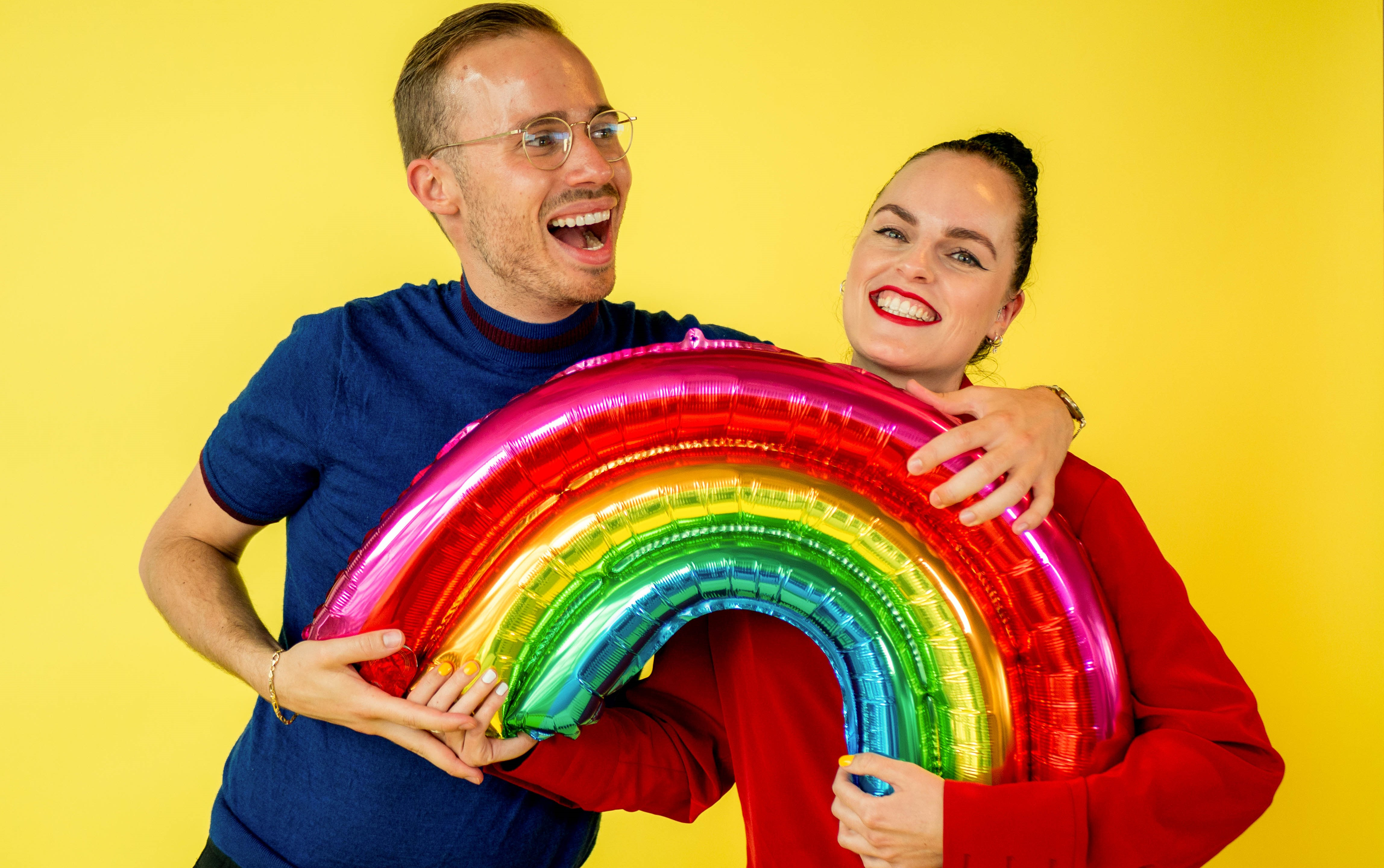 2 people hugging while holding an inflatable rainbow